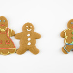 Frowning male gingerbread cookie standing separate from happy gi